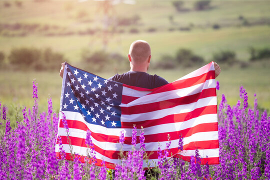 Patriot man holding the american flag on the 4th of July