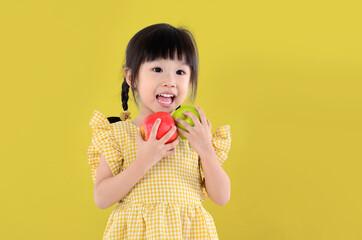 happy little asian girl holding green and red apple isolated on yellow background.