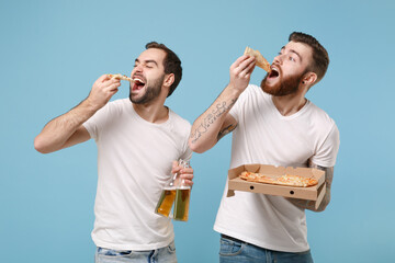 Two young men guys friends in white t-shirt posing isolated on pastel blue wall background. Sport leisure concept. Cheer up support favorite team with beer bottle, italian pizza in cardboard flatbox.