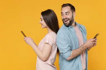 Excited smiling young couple friends guy girl in casual clothes isolated on yellow background. People lifestyle concept. Mock up copy space. Stand back to back using mobile phone typing sms message.