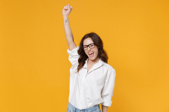 Overjoyed young brunette business woman in white shirt glasses isolated on yellow background. Achievement career wealth business concept. Mock up copy space. Clenching fist like winner, rising hand.