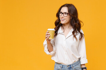 Smiling young business woman in white shirt glasses isolated on yellow wall background. Achievement career wealth business concept. Mock up copy space. Hold paper cup of coffee or tea, looking aside.