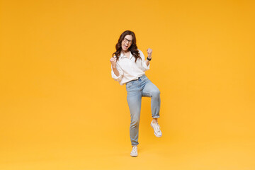 Happy young brunette business woman in white shirt glasses isolated on yellow background studio portrait. Achievement career wealth business concept. Mock up copy space. Clenching fists like winner.