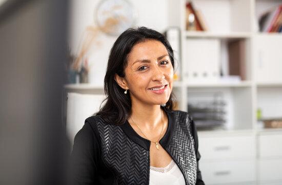Positive Peruvian female entrepreneur in office interior