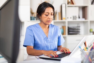 Female doctor working with laptop in clinic office