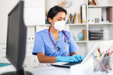 General practitioner woman in mask working on laptop