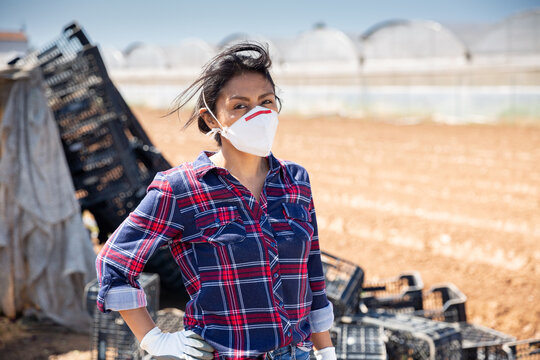 Hispanic female farmer in medical face mask