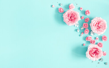Flowers composition. Frame made of rose flowers on blue background. Flat lay, top view, copy space