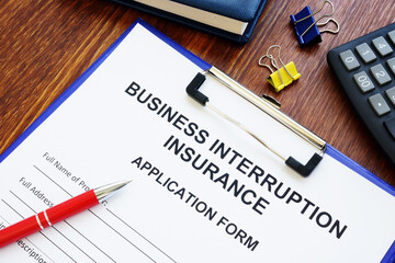 Business interruption insurance form and red pen for signing.