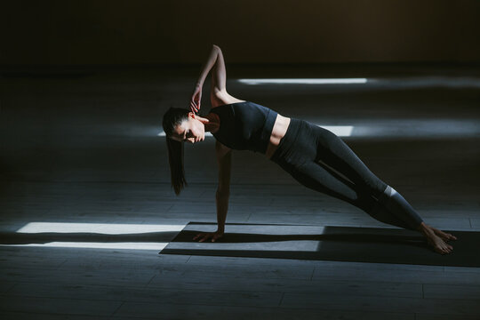 Young dedicated attractive slim yogi girl in Side Forearm Plank yoga pose. Yoga studio interior.
