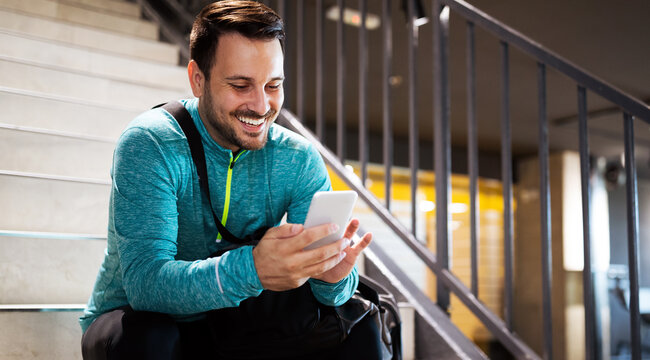 Portrait of young fit man athlete with mobile phone, bag after workout in gym
