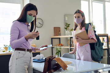 Mother with smartphone checking car key while getting ready with teenage daughter in mask to tutor during coronavirus