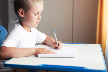 A school-aged boy sits at a desk and begins to draw on an empty white sheet of the album