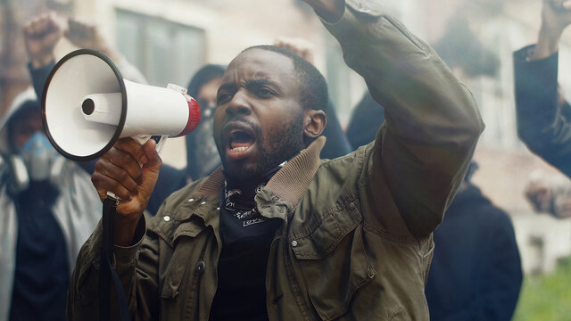 African-American young handsome man screaming in megaphone at protest for human rights outdoors in smoke. Group of people protesting at street. Strike against violence.
