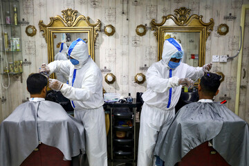 Barbers wearing protective suits provide hair cut service to the customers, in Dhaka