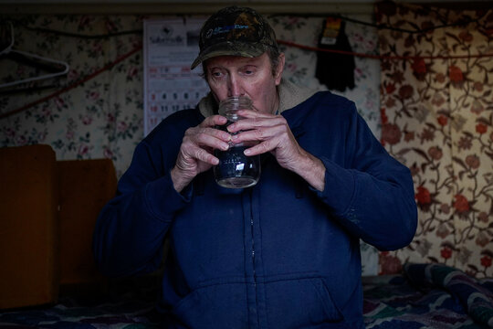 Hanson Rowe, a landowner who blames a leaky gas well on his property for health problems, drinks from a jar of moonshine, in Salyersville