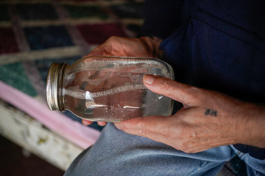 Hanson Rowe, a landowner who blames a leaky gas well on his property for health problems, holds a jar of moonshine, in Salyersville