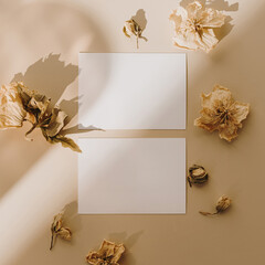 Blank paper sheet cards with mockup copy space and dry flower buds with sunlight shadow on beige background. Minimal business brand template. Flat lay, top view
