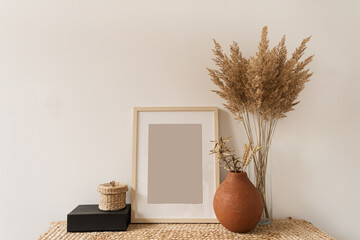 Blank photo frame with copy space, reeds bouquet in vase, rye in clay pot at white wall. Mockup template. Modern interior design concept.