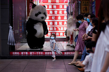 A little girl wearing face mask dances in front of a toy panda at a shopping area in Shanghai