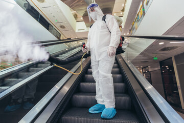 Professional workers in hazmat suits disinfecting indoor of mall, pandemic health risk, coronavirus