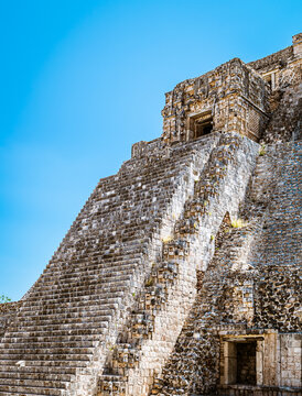 Close-up on the steep stair flight of the Pyramid of the Magician against the backdrop of a pale blue sky in an ancient Maya city of Uxmal, Yucatan, Mexico.