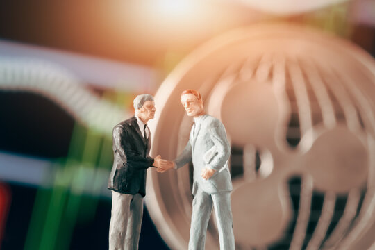 Business agreement concept: Two businessman figurine shaking hands in front of blurry stock market chart and shiny ripple coin. Partnership, success, investment, dealing concept.