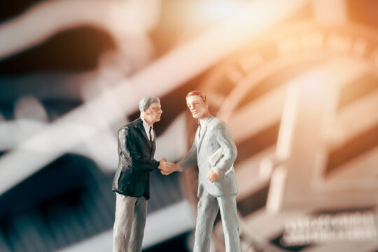 Business agreement concept: Two businessman figurine shaking hands in front of blurry stock market chart and shiny litecoin. Partnership, success, investment, dealing concept.