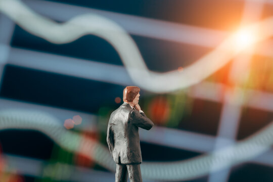 Concept of thinking businessman: Businessman figurine with hand on cheek deciding to make a decision while looking at the stock market chart on the background.