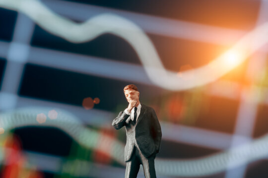 Concept of thinking businessman: Businessman figurine with  hand on cheek and deciding to make a decision while standing in front of stock market chart on the background.