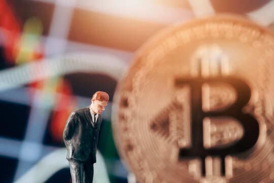 Cryptocurrency concept with thinking businessman: Businessman figurine with hands behind back, deciding to make a decision in front of  market chart and bitcoin.