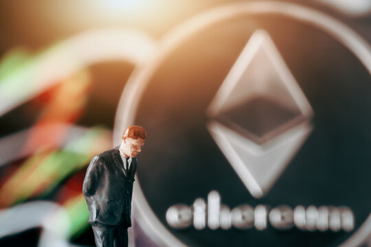 Cryptocurrency concept with thinking businessman: Businessman figurine with hands behind back, deciding to make a decision in front of  market chart and etherum.