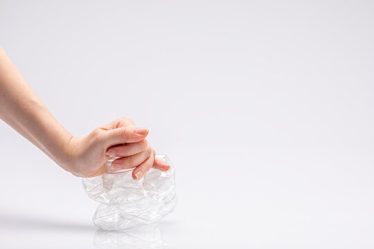 Close-up of a white people's hand crushing a crumpled plastic bottle in front of a white background