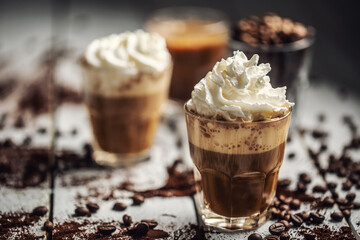 Black coffee with whipped cream in glass cups and spilled coffee beans