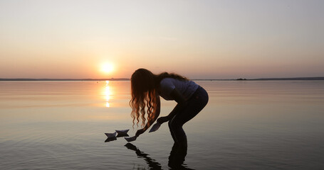 Silhouette of a girl with long curly hair letting a few paper boats go on the water. Toy ship sailing to the red sunset. Young woman dreaming during sunset.
