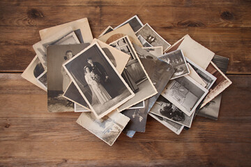 Wall Mural - old vintage monochrome photographs in sepia color are scattered on a wooden table, the concept of genealogy, the memory of ancestors, family ties, memories of childhood