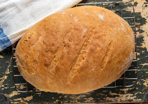 Chleb własnej roboty. Zdjecie z gory.  Domowe wypieki. Wyrob z maki pszennej. Smacznie i zdrowo. Swieze pieczywo na stole w kuchni. Dla wegetarian. Na starym stole.