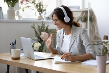Smiling young Caucasian woman in headphones take online educational course or training on laptop...