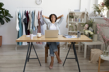 Relaxed young Caucasian female fashion designer or stylist rest in chair at desk daydreaming, happy businesswoman relax at workplace sleep or nap, relieve negative emotions, stress free concept Wall mural