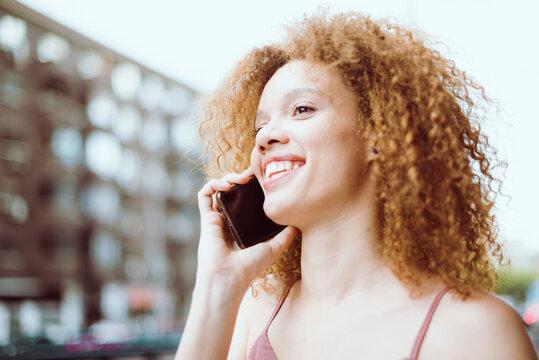 Chica sonriente hablando por teléfono en la calle. Concertando una cita telefónica