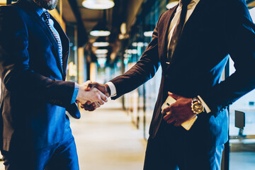 Cropped view of trust businessman greeting corporate partner.Two colleagues handshaking after successful deal standing in office interior.  Partnership meeting concept. Congratulation and acquisition