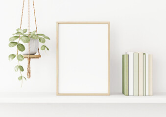 Interior poster mockup with vertical wooden frame on the shelf with green plant in hanging pot, books and trendy decoration on empty white wall background. A4, A3 size. 3D rendering, illustration.