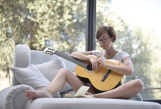 Lady with short black hair and glasses playing the guitar on the couch