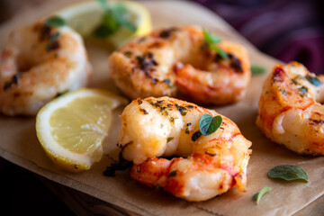 Roasted shrimps with lemon and herbs, healthy seafood meal