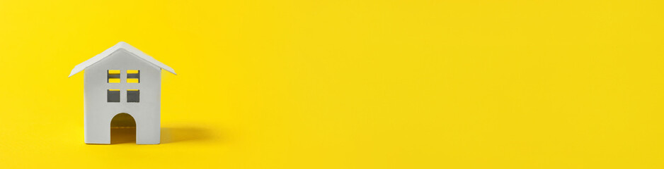 Simply minimal design with miniature white toy house isolated on yellow colourful background. Mortgage property insurance dream home concept. Flat lay top view copy space banner.