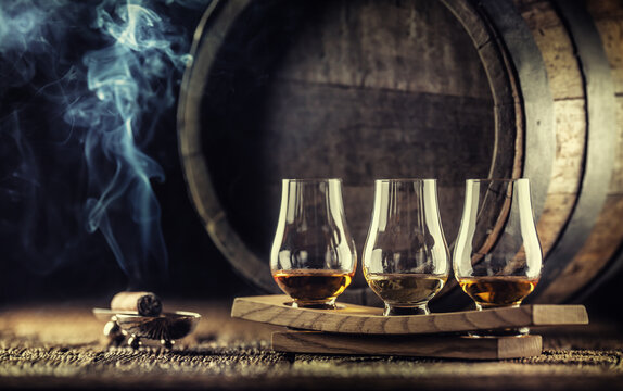 Glencairn whiskey tasting cups on a wooden serving, with a whisky barrel in the dark background and a smoking cigar next to it