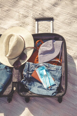Travel.Todler sits near a suitcase with things and dreams of a vacation traveling after quarantine,...