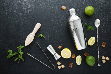 Barman equipments with limes, lemons and sugar on black wooden table