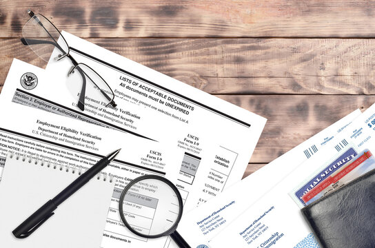 USCIS form I-9 Employment eligibility verification lies on flat lay office table and ready to fill. U.S. Citizenship and Immigration services paperwork concept