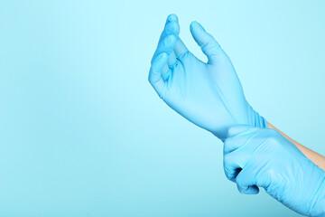 Doctor hands in gloves on blue background